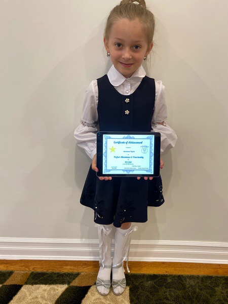 child in uniform holds up her certificate