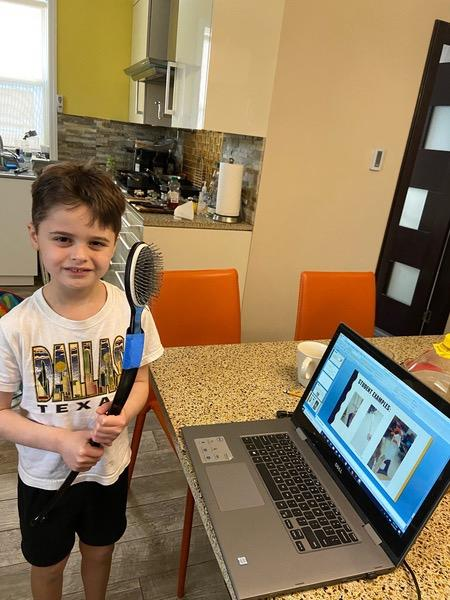 boy holds his creation near his laptop