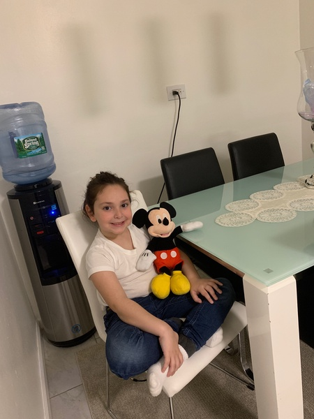 Mickey Mouse sitting with a child at the table