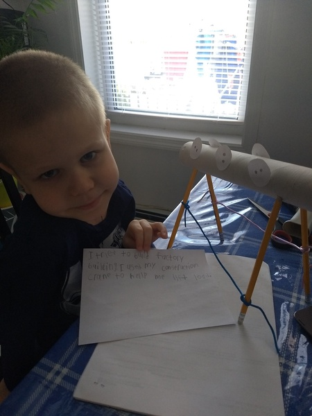 the child smiles at the blue table next to his project