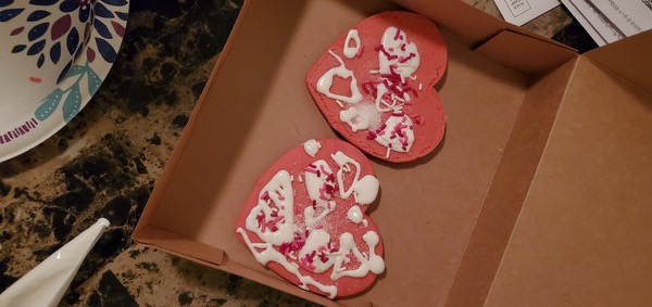 two pink heart shaped cookies with white icing