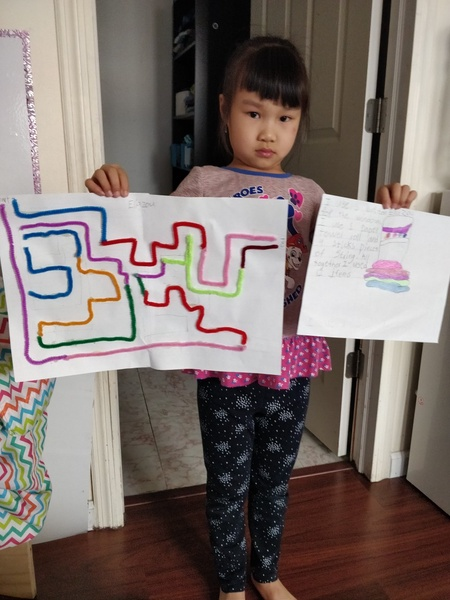 the girl holds her artwork and her maze