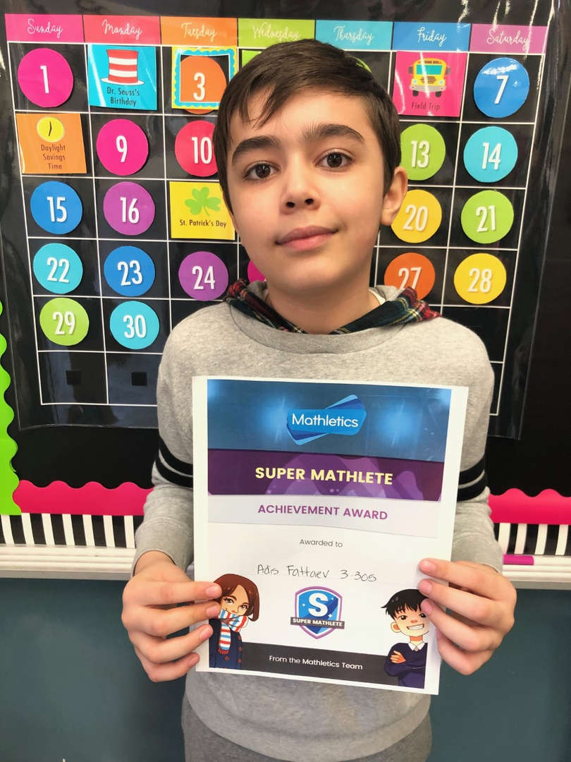 A student hold his certificate for being a top mathletics winner.