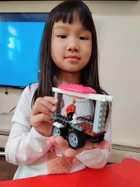 Girl shows her Lego creation