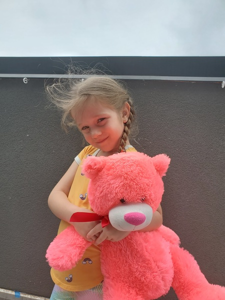 little girl holds a large pink bear as she smiles