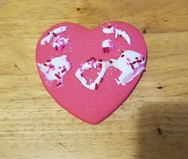 pink heart cookie with a face decorated in icing