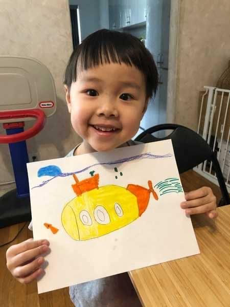 child holds submarine artwork