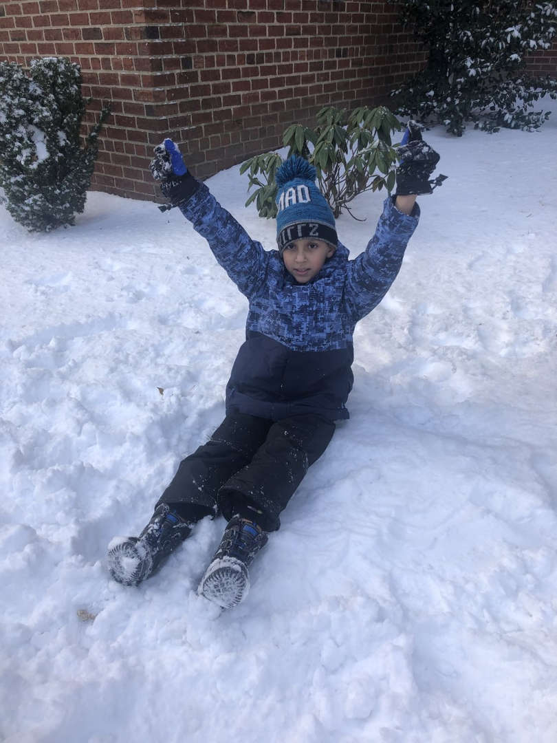 boy sitting in the snow with his hands up