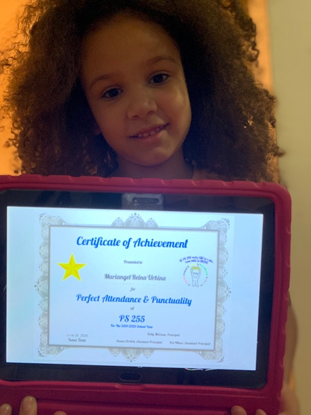 child holds her certificate on an iPad with a pink case