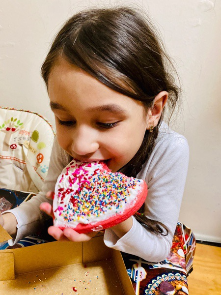 girl takes a bite of her heart shaped decorated cookie