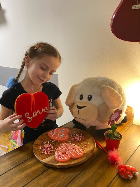 girl has a heart shaped snack with her teddy bear