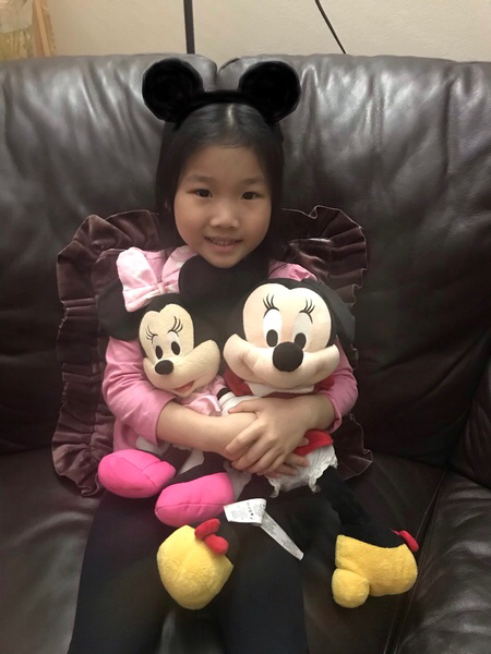 girl on couch hugging mickey and Minnie