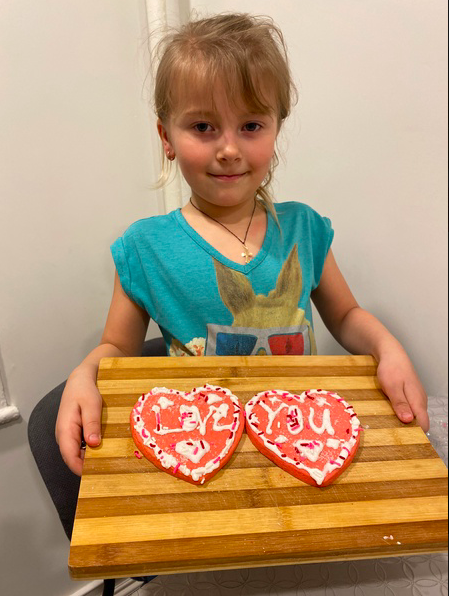 girl holding tray with 2 cookies