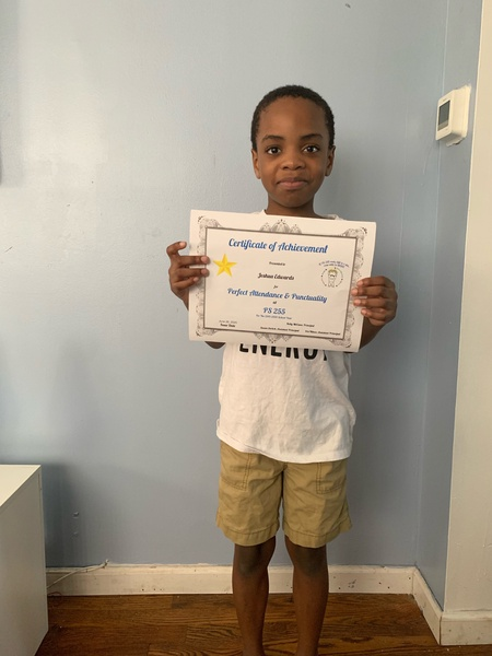 child holds a large printout of his certificate