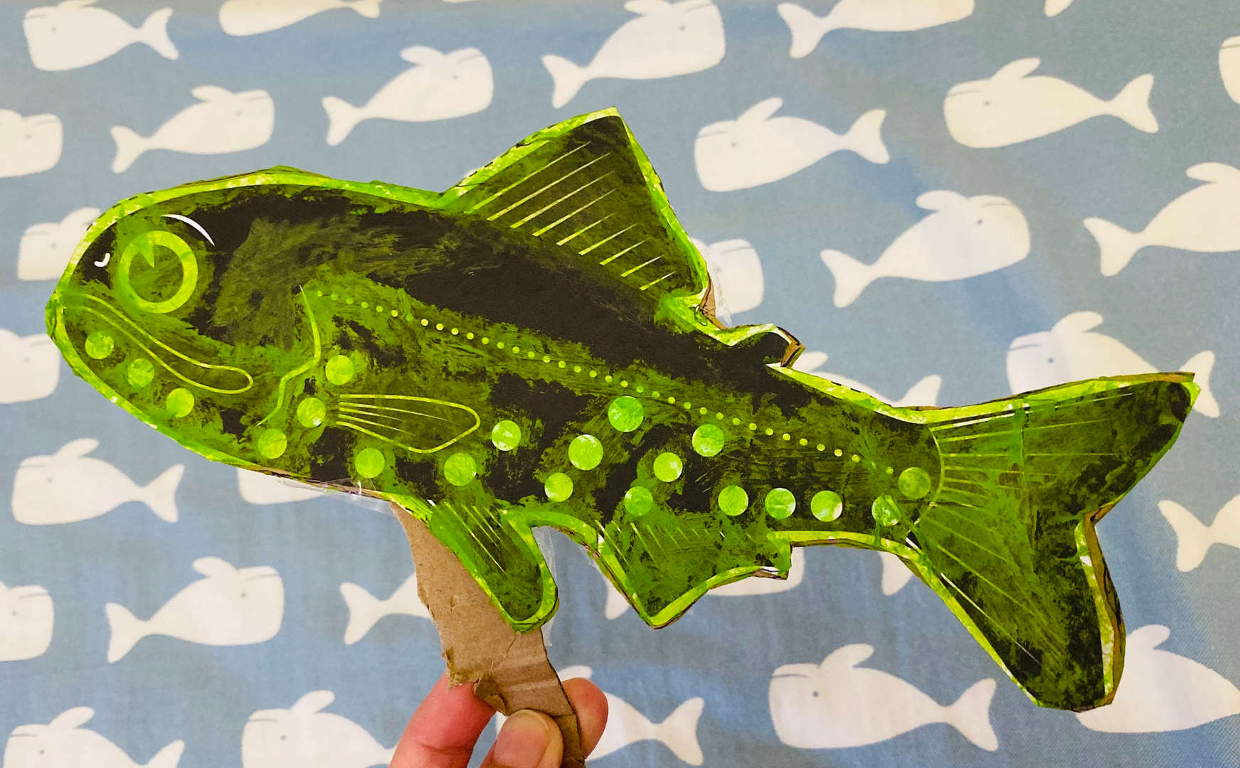a fish made using green paper and black paint