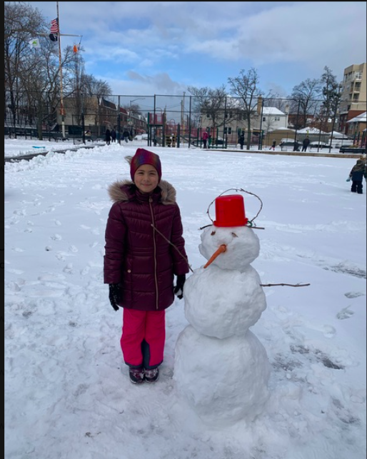 a girl next to a snowman with a red hat
