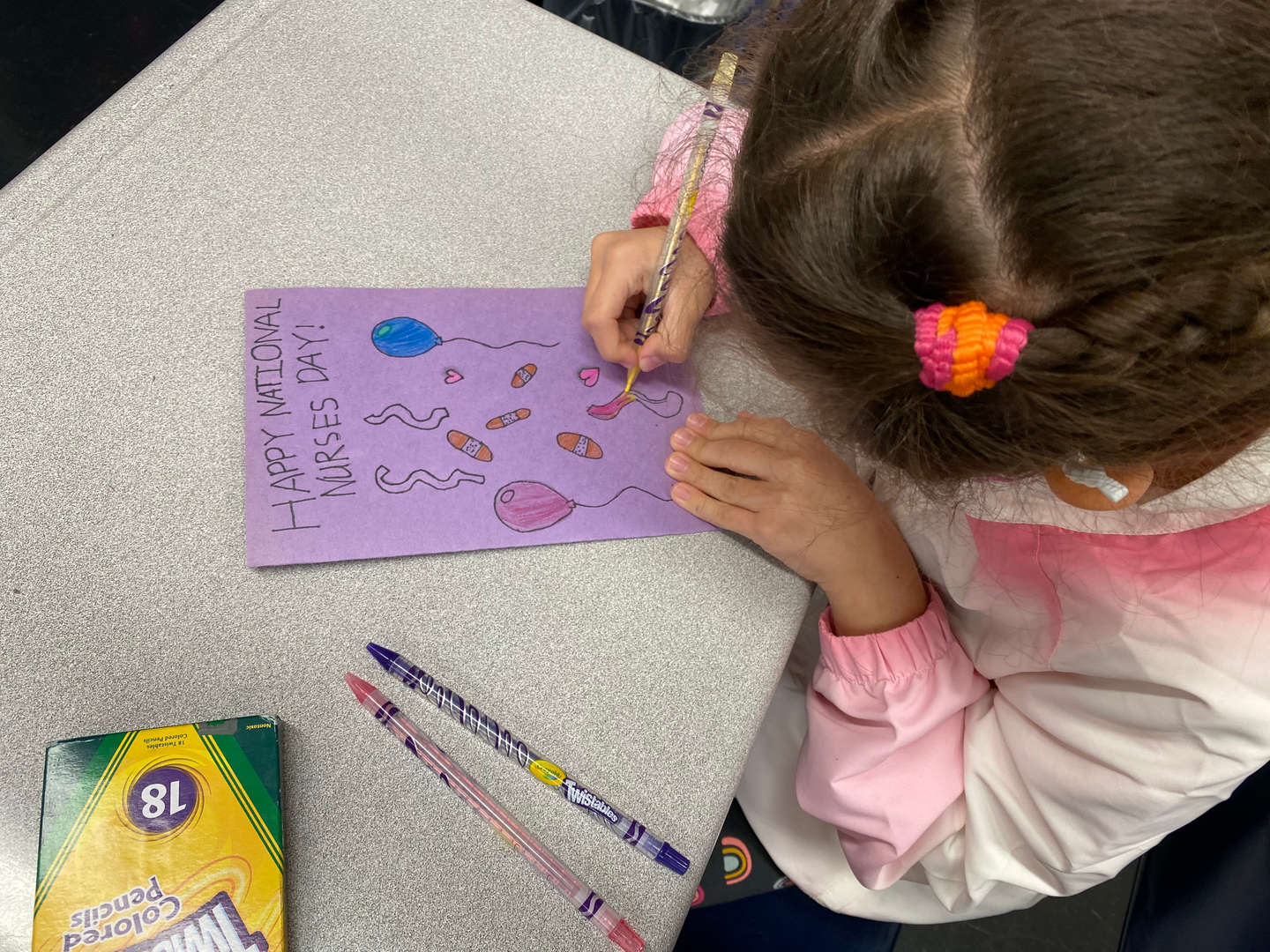 a student drawing a purple thank you card