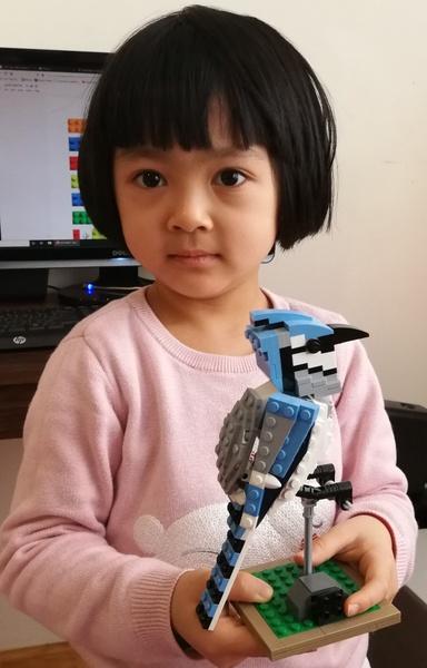 girl holds bird made of legos