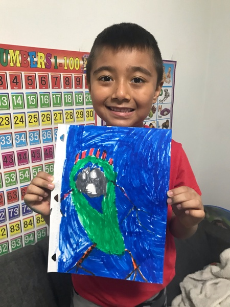child standing holding drawing with the entire page colored in