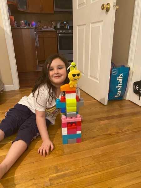 Smiling girl shows Lego building she built