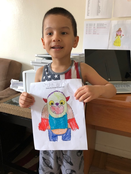 child holds his monster drawing with a body
