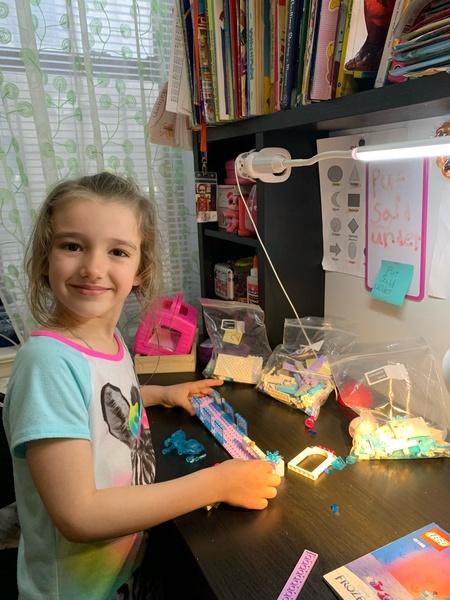 Girl builds using legos