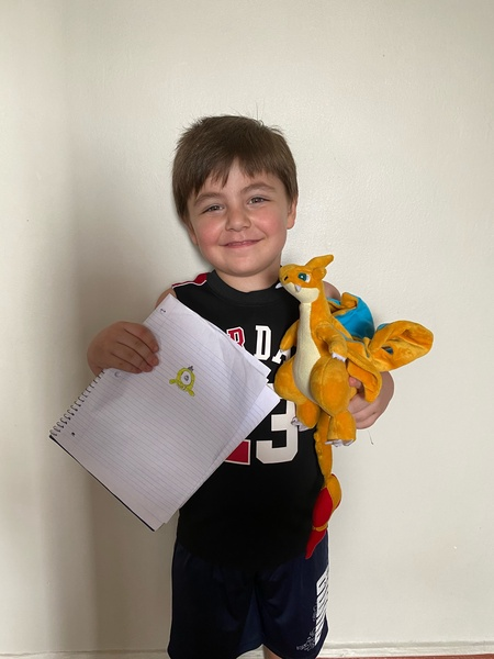 child holds book with his drawing and a monster stuffed animal