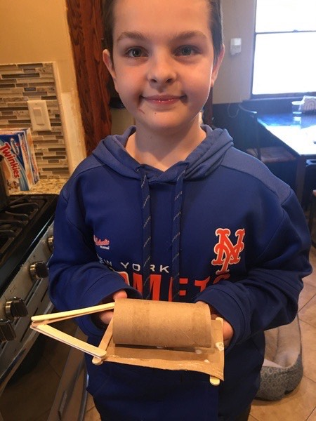 the child wears a met shirt and shares his project
