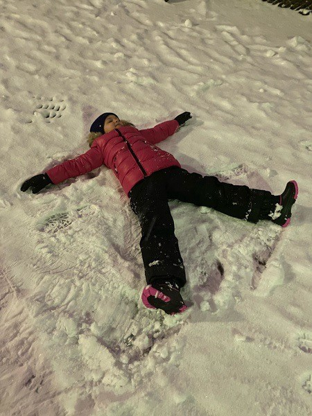 child making a snow angel with a red coat