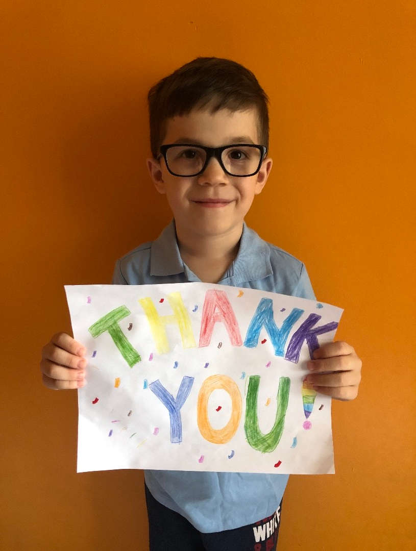 child holds a sign with thank you written in rainbow colors