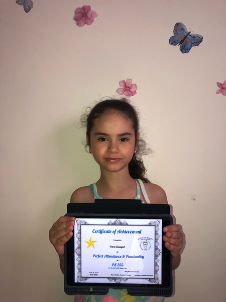 girl holds certificate near flower decal on wall