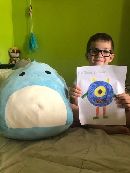 standing holding drawing of a one eyed monster while next to a stuffed animal
