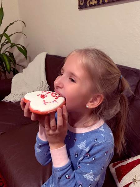 girl eating her decorated cookie
