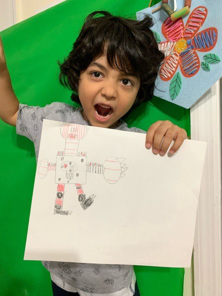 child makes a monster face while holding his monster picture