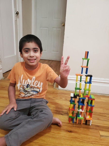 boy in an orange shirt gives a peace sign next to his creation