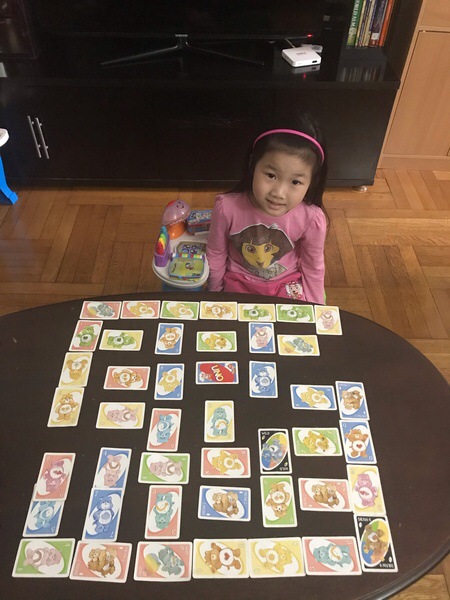 the child sits at the table with all of the pieces for her game