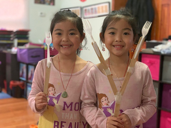 twins hold their creations while dressed alike