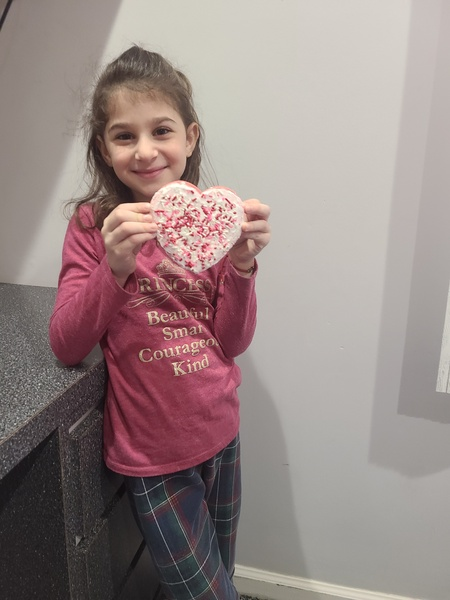 child holds her heart cookie