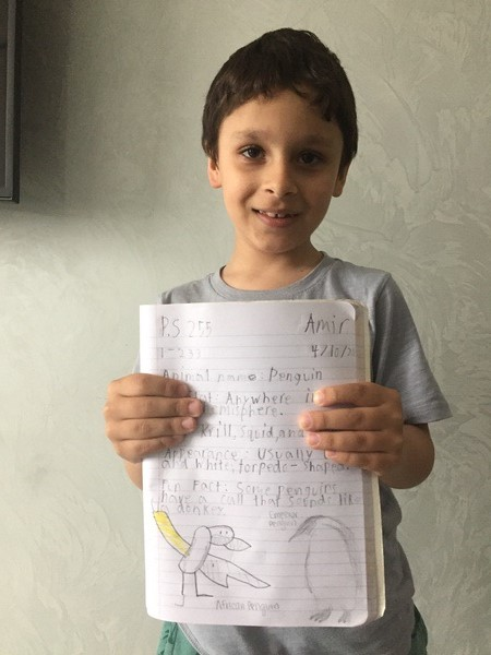 boy holds his work about the zoo