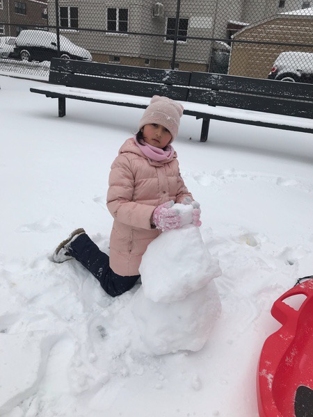 a girl in a pink coat building a snowman