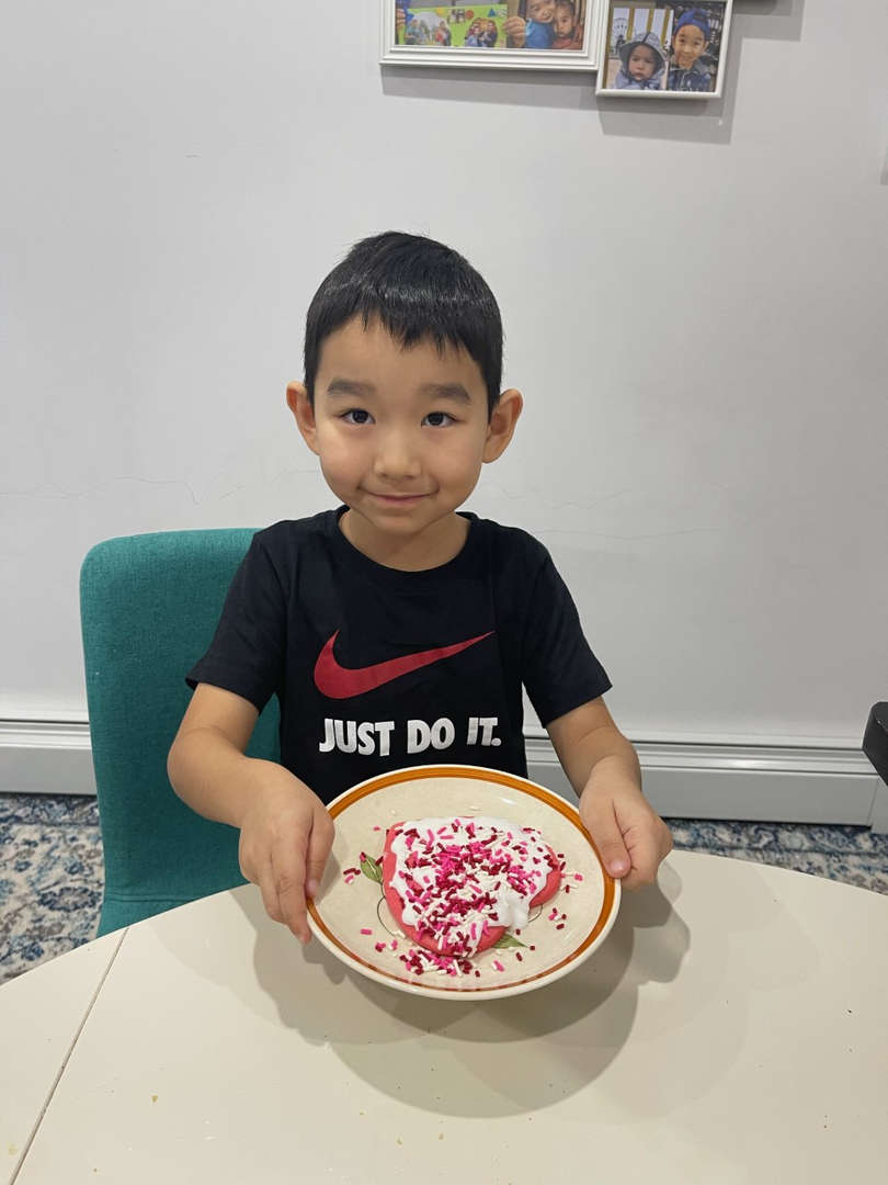 boy in Nike shirt showing his decorated cookies