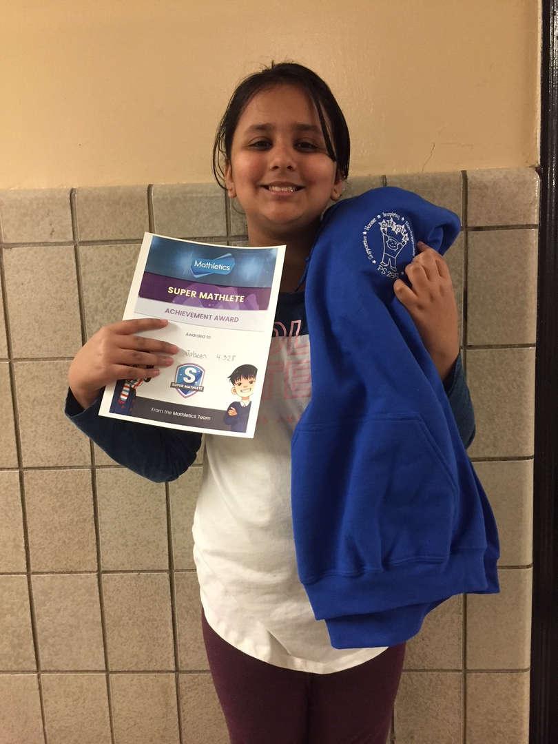 Girl holds certificate and sweatshirt.