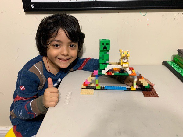 the child gives a thumbs next to his lego bridge
