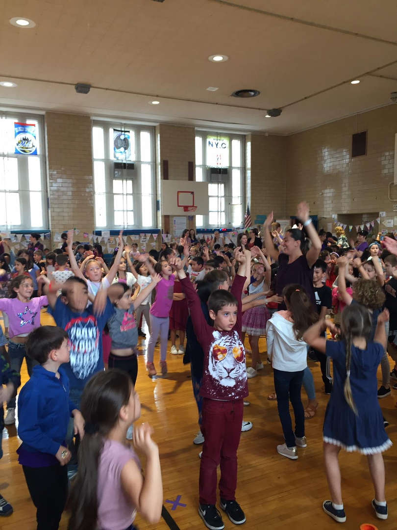 Students have their hands in the air while listening to music.