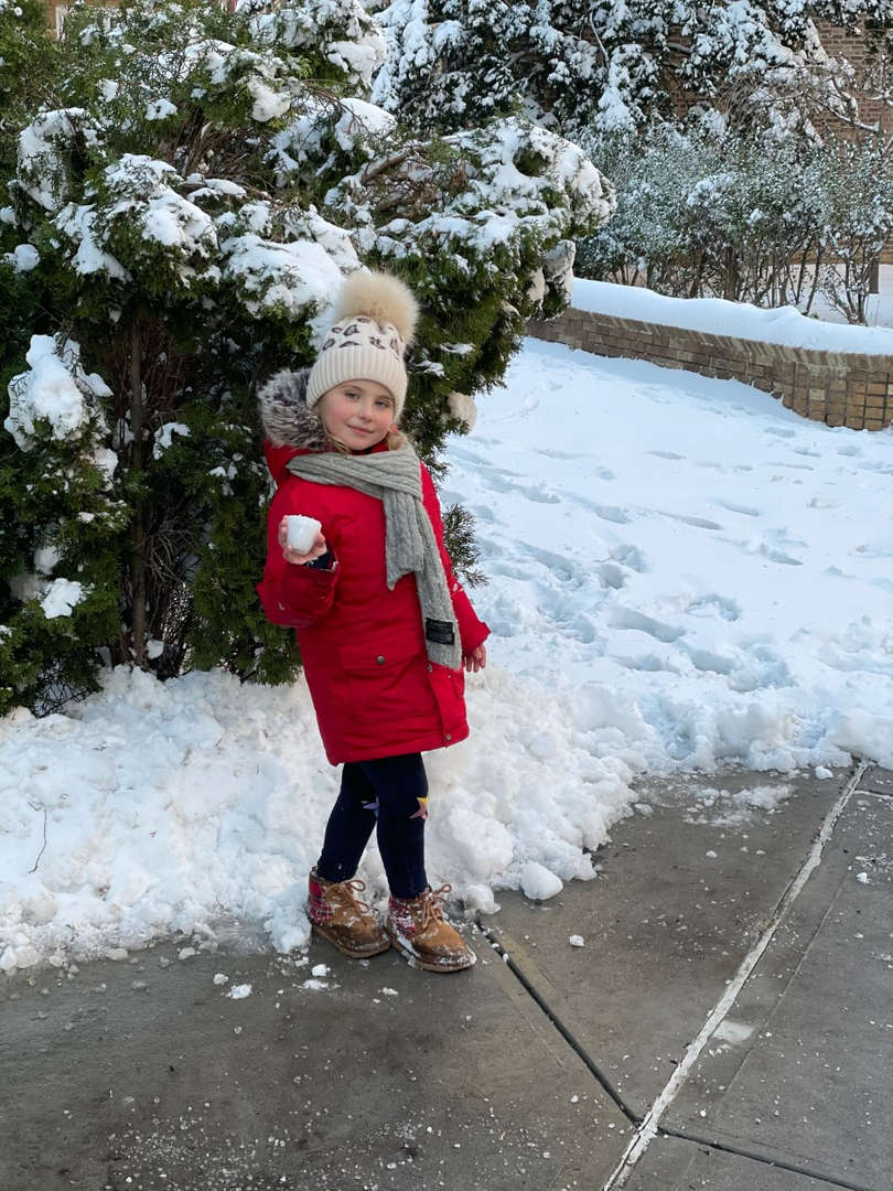 girl in red coat carrying snow