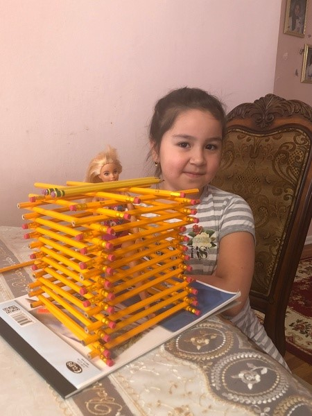 the girl smiles at her pencil building