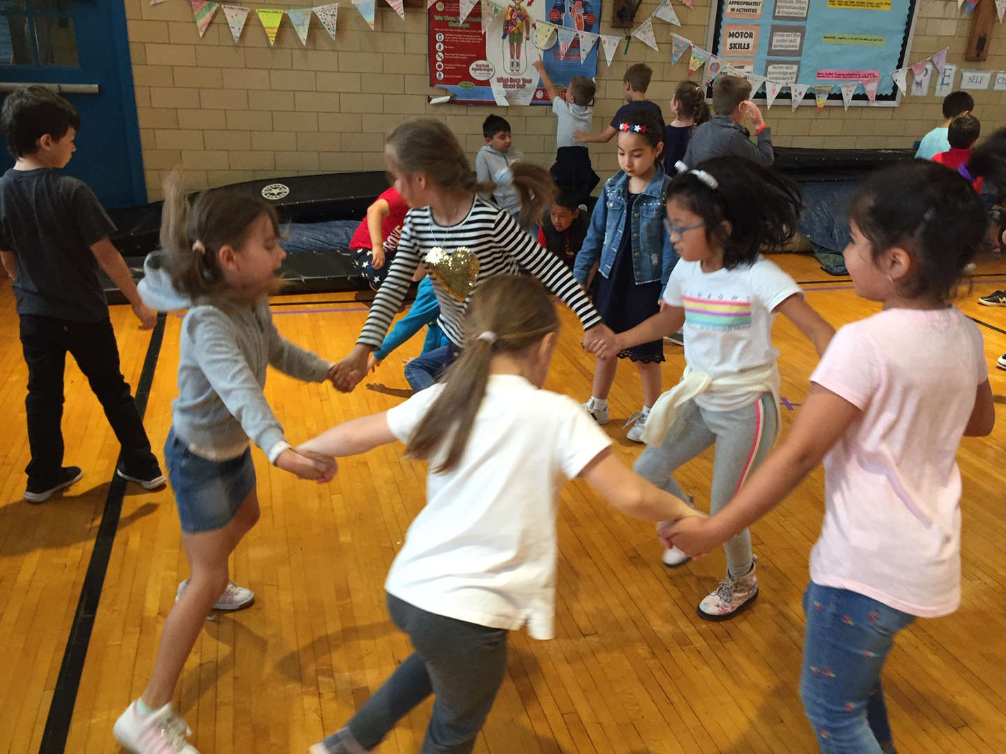 Students form a circle to dance to the music.