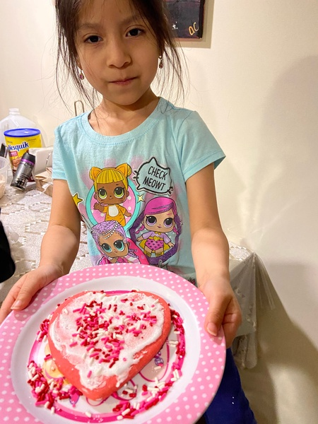 girl shows her decorated cookies on a pink and white plate