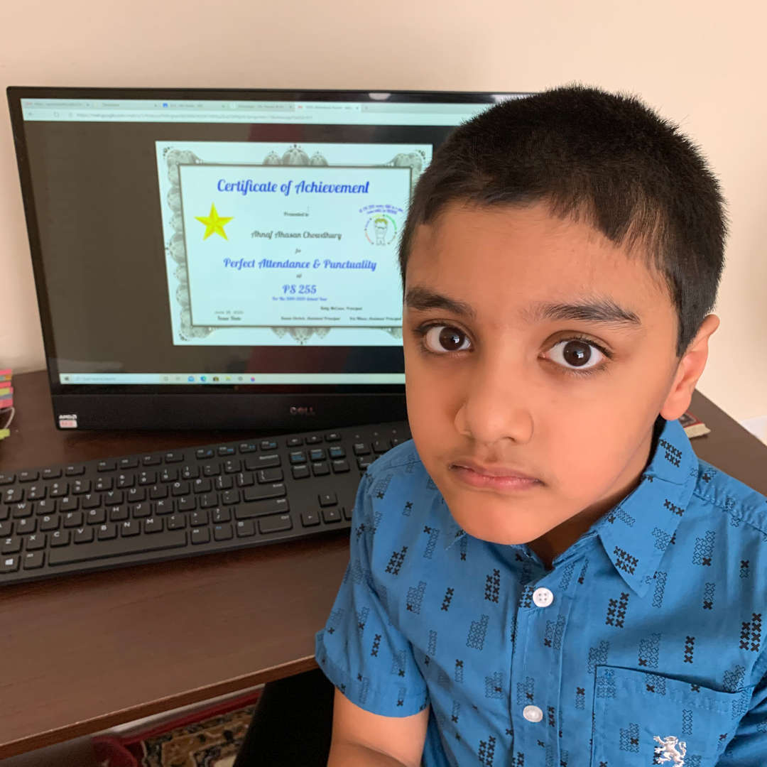 child sits next to certificate displayed on a computer screen