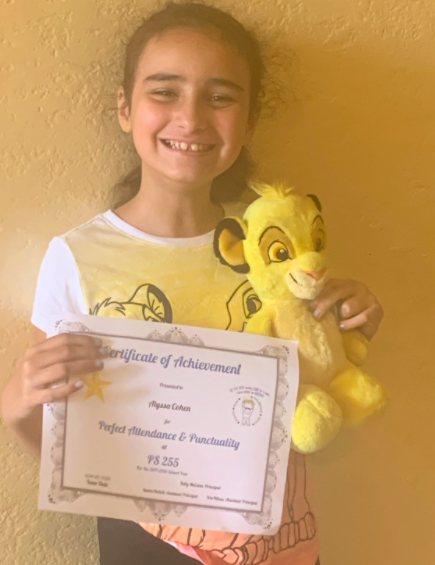 child holding her certificate with a Simba stuffed animal